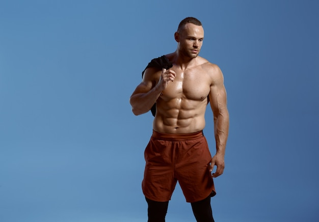 Strong male athlete, photo shoot in studio, blue background. one man with athletic build, shirtless sportsman in sportswear, active healthy lifestyle