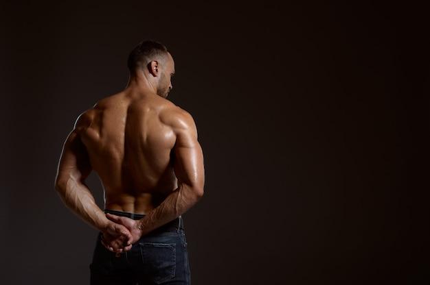 Сильный спортсмен-мужчина позирует в студии, вид сзади