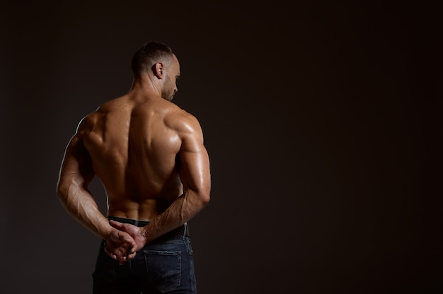 Strong male athlete poses in studio, back view