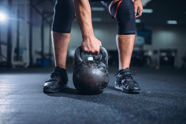 Strong male athlete prepares for exercise with kettlebell lifting.