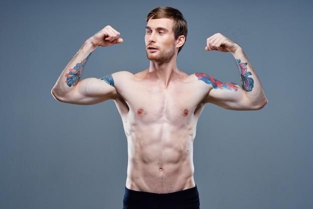 腕の筋肉を強化し、ボディービルダーのフィットネスを入れ墨した強い男性アスリート