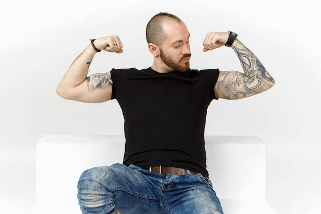 Forte bodybuilder maschio con stoppie, pettinatura elegante e braccia tatuate, dimostrando i suoi bicipiti, tendendo i muscoli dopo l'esercizio di sollevamento pesi, sentendosi orgoglioso di se stesso, in posa isolato in studio