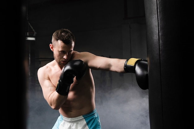 Strong male boxer training for a competition