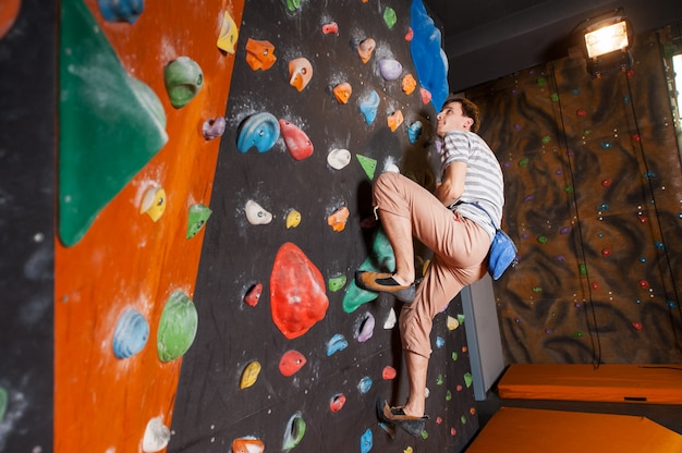 Strong male climber on boulder climbing wall indoor