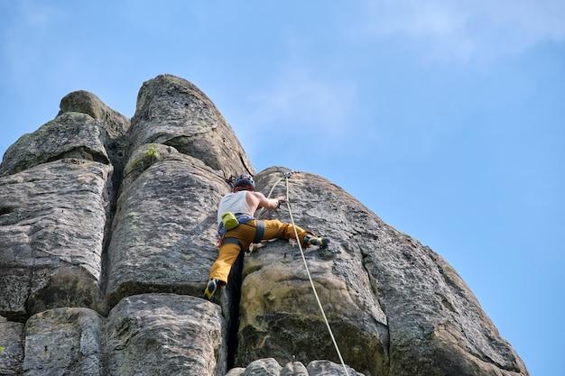 바위 산의 가파른 벽을 등반 하는 강한 남성 산악인. 어려운 경로를 극복하는 스포츠맨. 익스트림 스포츠 취미 개념에 참여합니다.