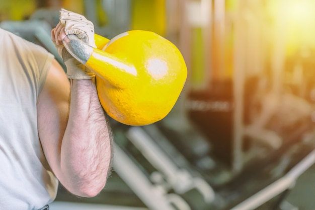 Strong male hand with yellow kettlebell in gym fitness sports center.