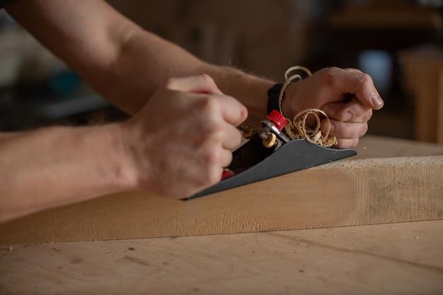 強い男性の手が飛行機を持ち、それを使って木片を加工します。