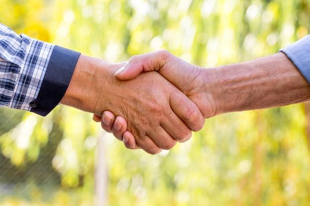 屋外で強い男性の握手。あいさつで握手_