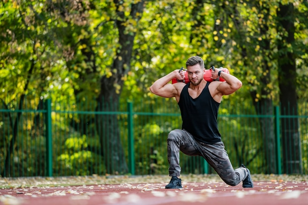 Strong male, outdoor fitness work. lifting heavy tools. handsome sportsman. young bodybuilder. stands on one knee and lifts 10 kilo weight.