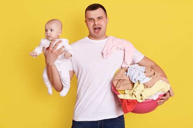 Strong male in white casual t shirt holding her new born baby and basin in hands, doing laundry