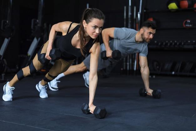 체육관에서 판자 위치에 아령을 들고 있는 강한 남자와 여자.