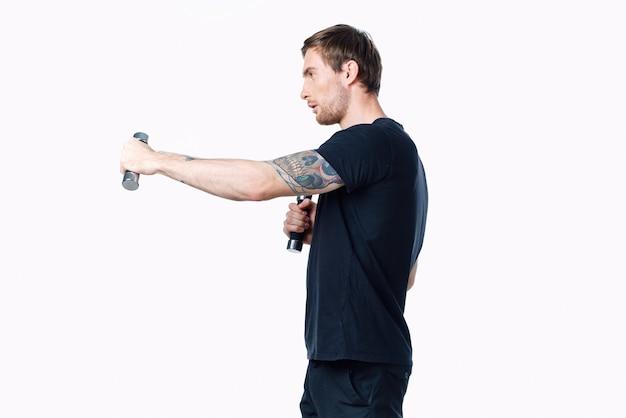 Сильный человек-спортсмен в черной футболке делает упражнения с гантелями в руках фитнес