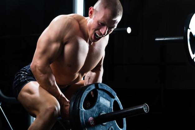 Сильный мужчина - культурист с гантелями в тренажерном зале, упражнения со штангой