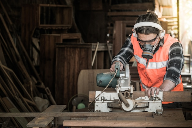 Strong man carpenter using table saw industrial work concept