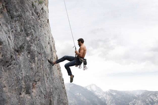 Strong man climbing on a mountain with safety equipment