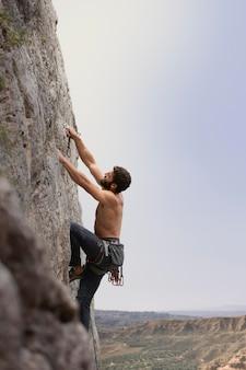 Strong man climbing on a mountain