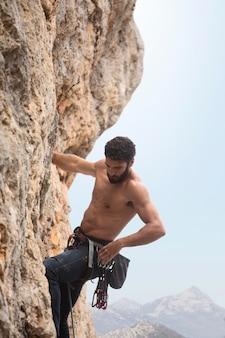 Uomo forte che si arrampica su una montagna