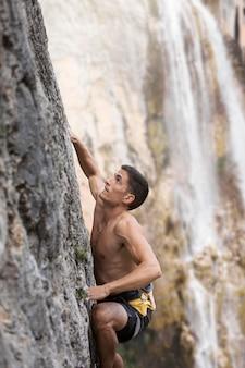 안전 장비와 함께 산에 등반 하는 강한 남자