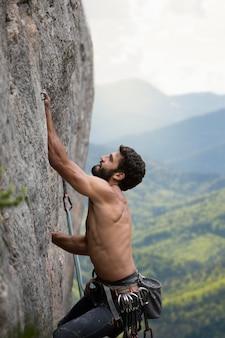 특별한 안전 장비로 등반하는 강한 남자
