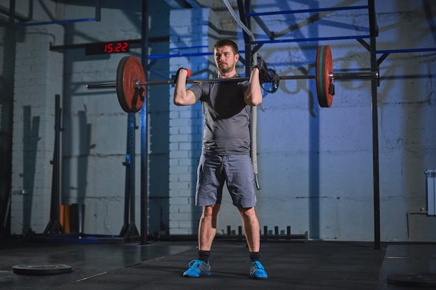 Strong man doing an exercise with a barbell in the gym