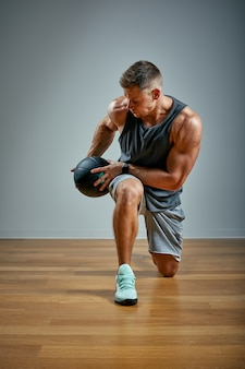 Strong man doing exercise with med ball. man perfect physique on grey. strength and motivation.