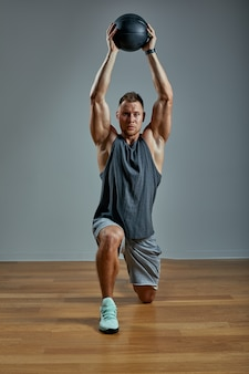 Strong man doing exercise with med ball. photo of man perfect physique on grey background. strength and motivation.