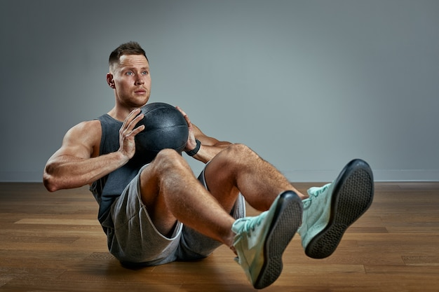 Strong man doing exercise with med ball. photo of man perfect physique on grey space. strength and motivation.