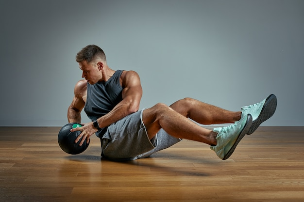 Strong man doing exercise with med ball. photo of man perfect physique on grey wall. strength and motivation.