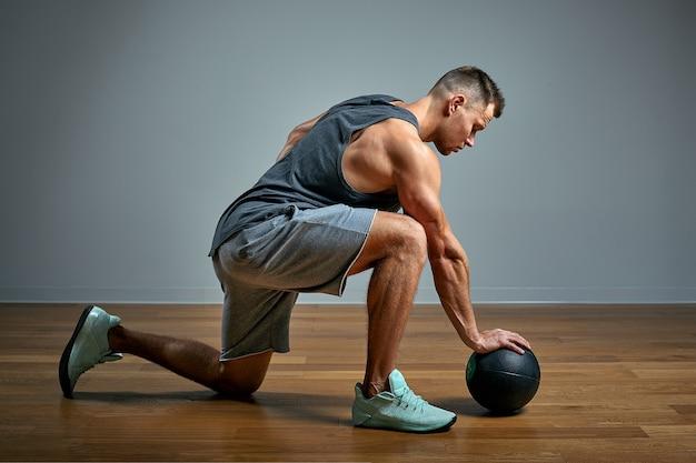 中程度のボールで運動をしている強い男。灰色の背景に男の完璧な体格の写真。強さとモチベーション。