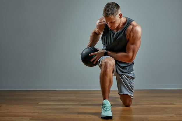 Medボールで運動をしている強い男。灰色の壁に男の完璧な体格の写真。強さと動機。