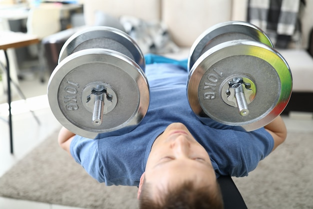 Strong man doing exercises with dumbbells on carpet