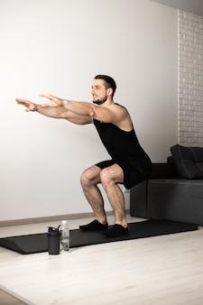 Сильный мужчина делает упражнения на корточки дома в своей просторной и светлой квартире с минималистичным интерьером. концепция здорового образа жизни, благополучия и деятельности. черная спортивная одежда.