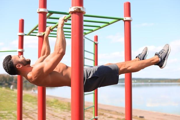 鉄棒で静力学運動をしている強い男は、晴れた日に屋外でトレーニングをしています。
