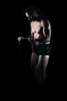 Сильный мужчина тренируется с резинкой