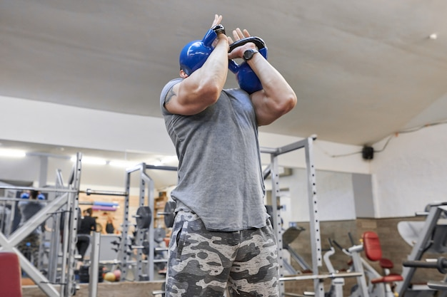 Strong man exercising with kettlebells in gym, weight training