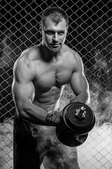Strong man on fence with dumbbell