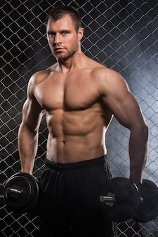 Strong man on fence with dumbbells