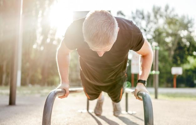 Сильный парень тренируется и делает отжимания с турником с солнечным светом на стадионе на открытом воздухе. мужчина во время тренировки для рук и груди. спортсмен, тренирующийся