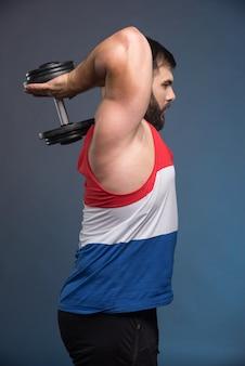 Сильный мужчина держит гантель на синей поверхности.
