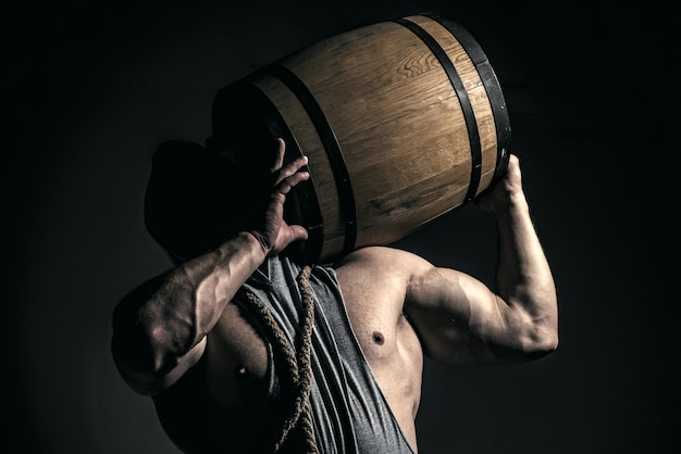Strong man holds barrel isolated on black