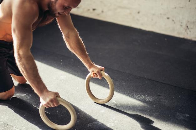 Сильный человек делает отжимания кольцами.