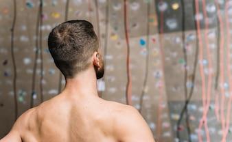 Strong man looking at climbing wall