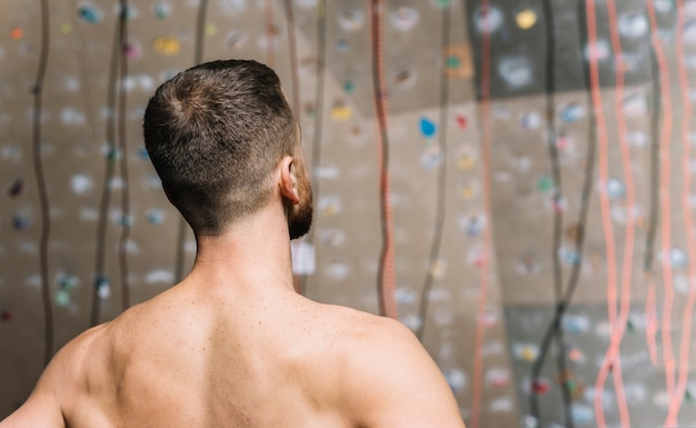 Strong man looking at climbing wall