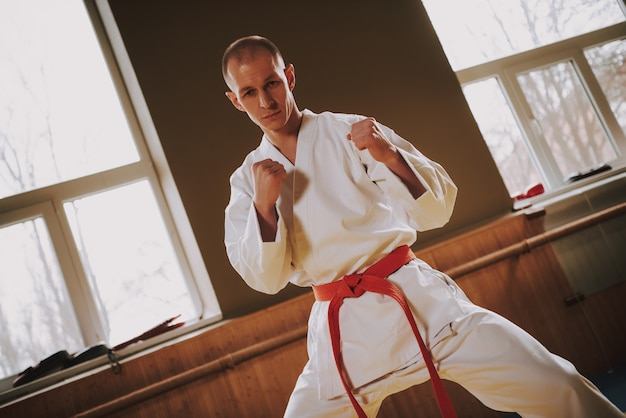 Strong man martial arts fighter in white training moves.