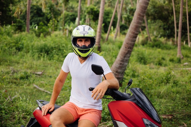 赤いバイクと熱帯のジャングルフィールドの強い男