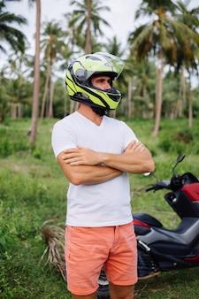 Сильный человек на поле тропических джунглей с красным мотоциклом