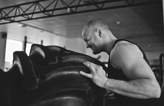 強い男は大きな重いゴム製の車輪を拾います。ファンクショナルトレーニング