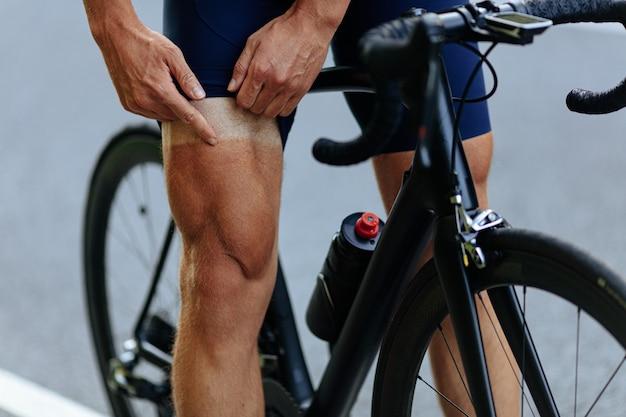 야외에서 사이클링하는 동안 태양이 타는 후 그의 다리에 손가락으로 가리키는 강한 남자.