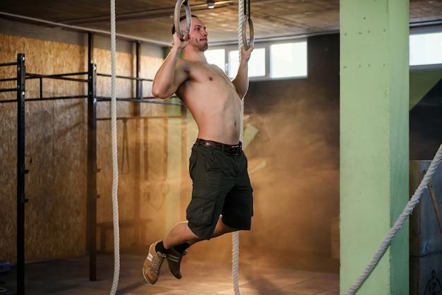 強い男は、近代的なジムで体操リングにプルアップします。ウォームアップ演習。