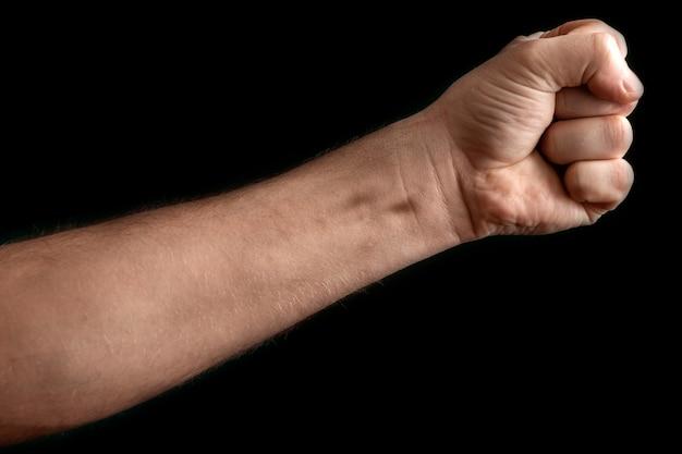 Strong man raised his fist on black
